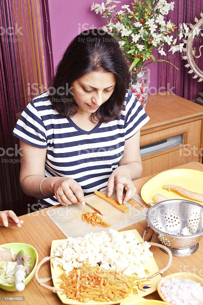 Indian Woman Preparing food cutting vegetables royalty-free stock photo