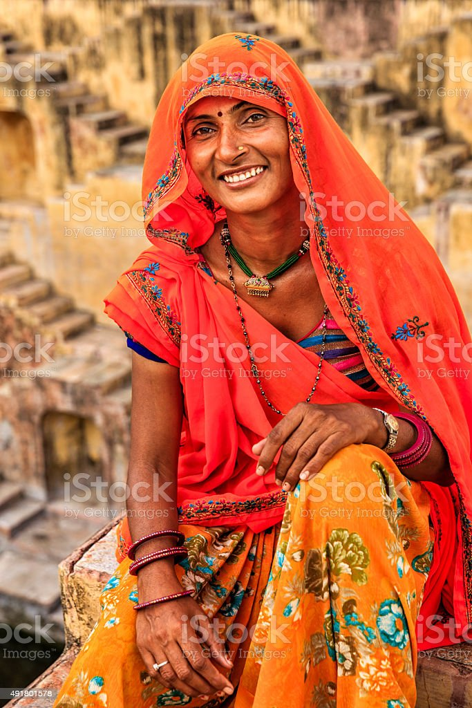Indian woman resting inside stepwell in village near Jaipur, India stock photo