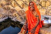 Indian woman resting inside stepwell in village near Jaipur, India