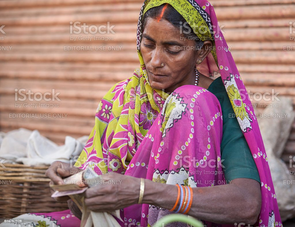 Indian woman seller in farmers market counting money stock photo