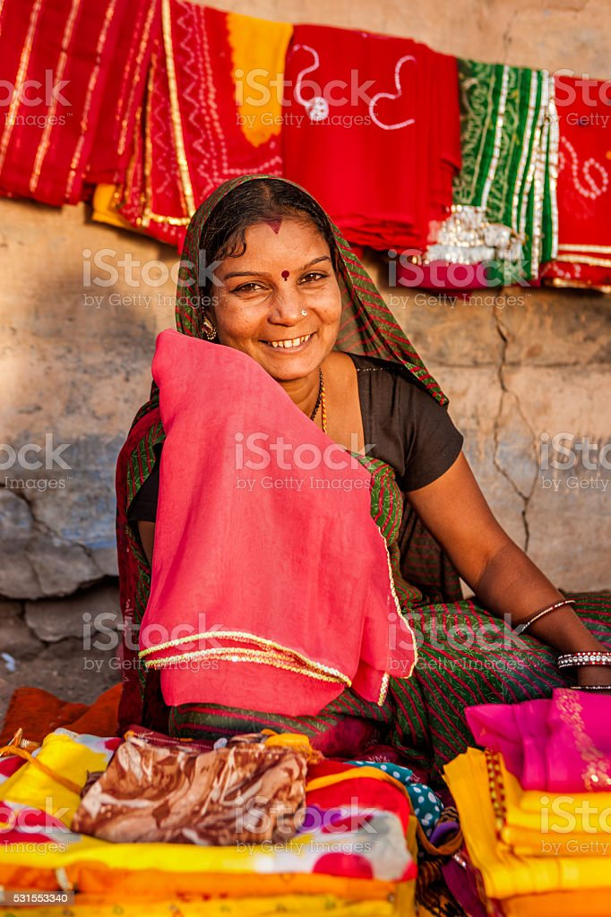 Indian woman selling colorful fabrics stock photo