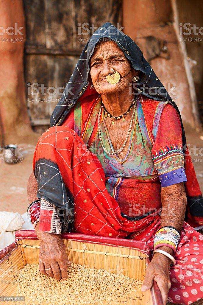 Indian woman sifting wheat grains in Bishnoi village, Rajasthan. stock photo