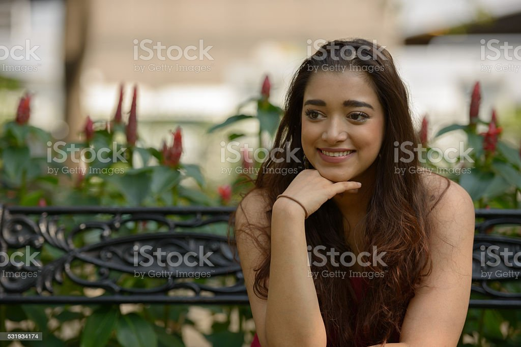 Indian woman sitting on park bench stock photo