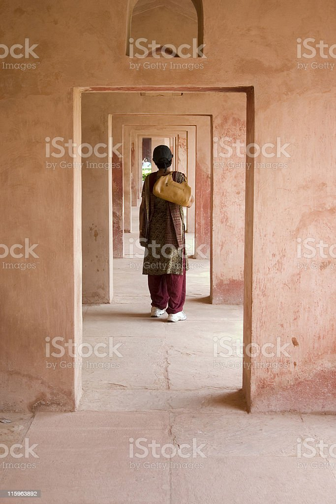 Indian Woman traveler looking at corridors of building Taj Mahal stock photo