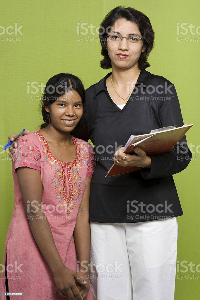 Indian Woman Volunteer offering helping hand to a rural girl royalty-free stock photo