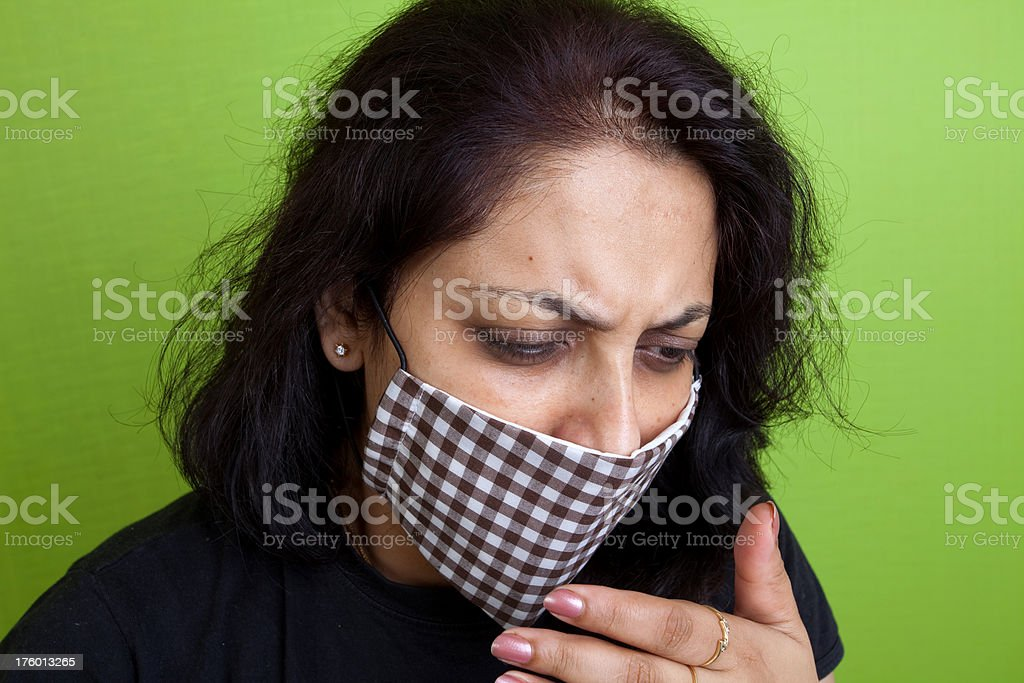 Indian woman wearing a mask against swine Flu coughing stock photo