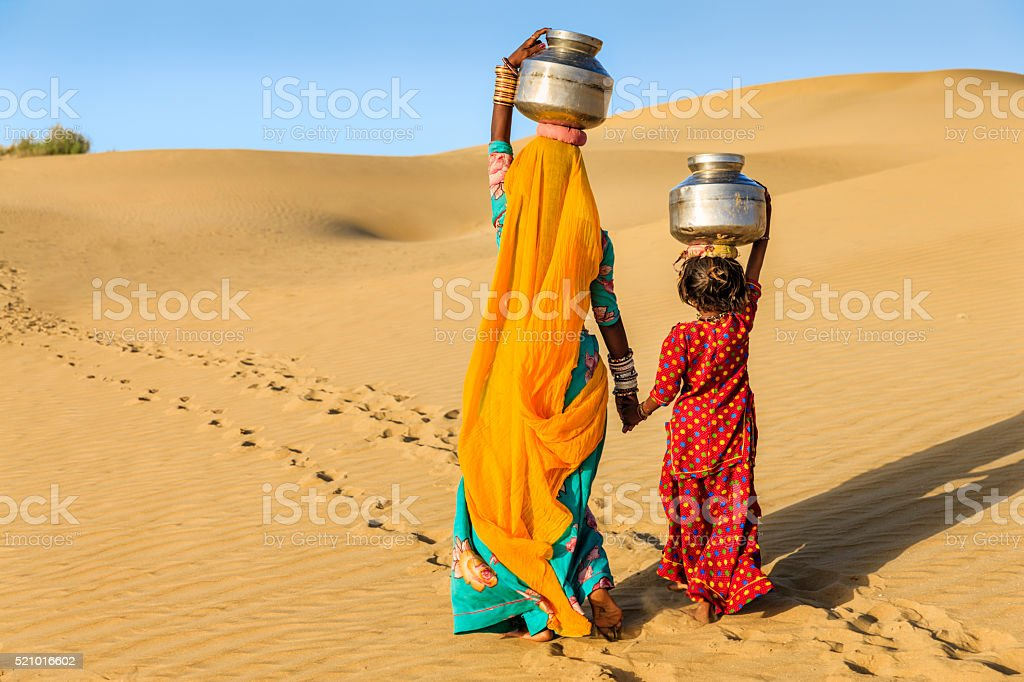 Indian woman with little daughter carrying water from well stock photo