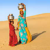 Indian woman with little daughter carrying water from well