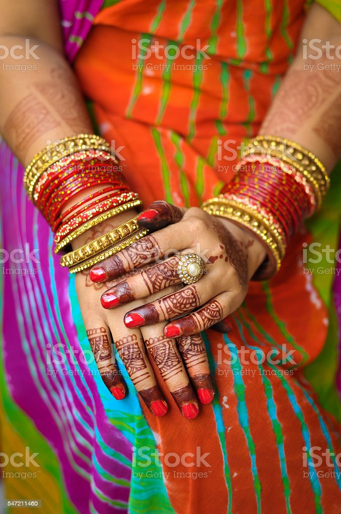 Indian woman's hand with henna tattoo and traditional bangles stock photo