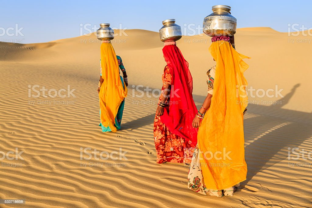 Indian women carrying on their heads water from local well stock photo
