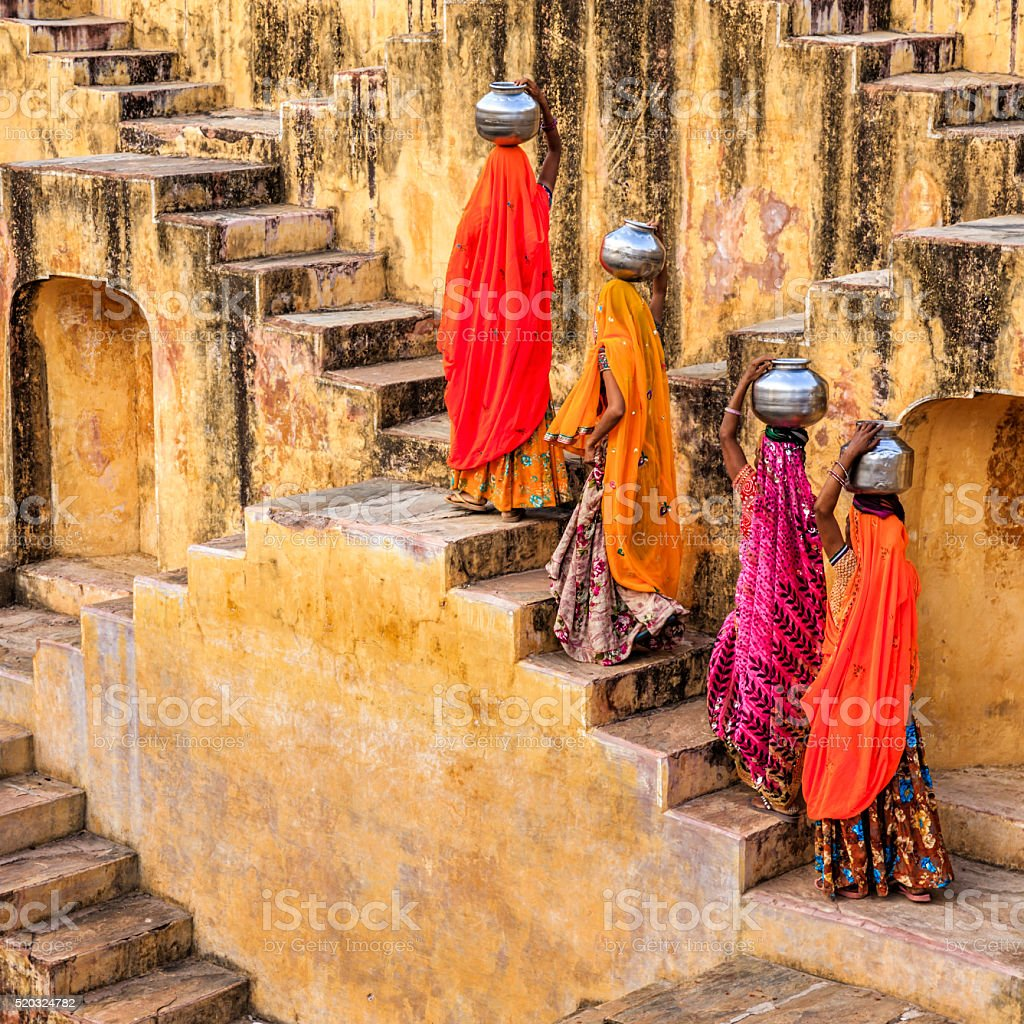 Indian women carrying water from stepwell, Rajasthan stock photo