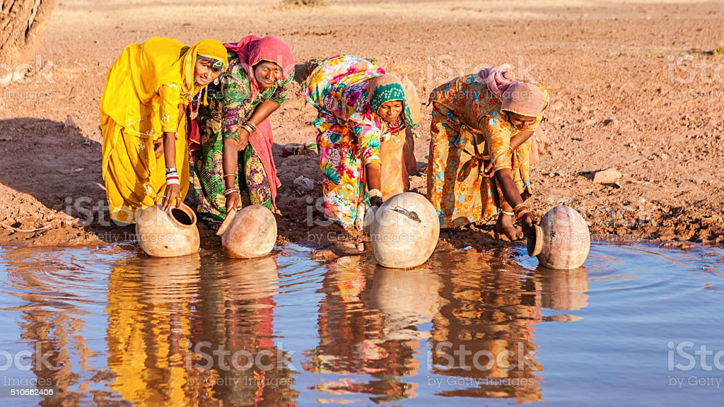 Indian women collecting water from a lake, Rajasthan stock photo