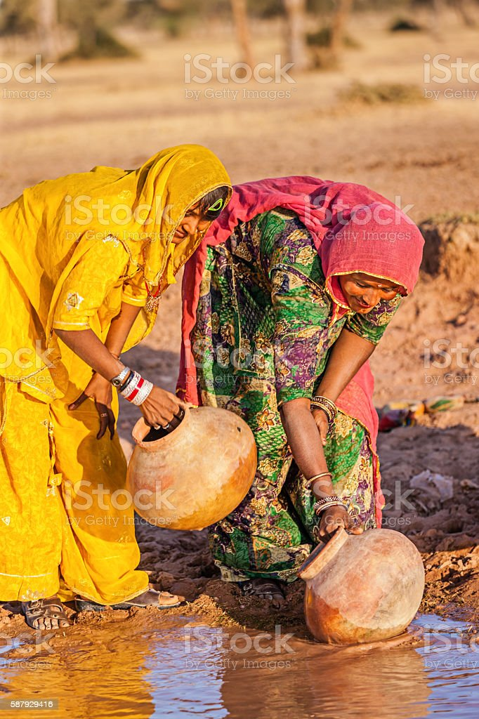 Indian women collecting water from local lake,Rajasthan stock photo