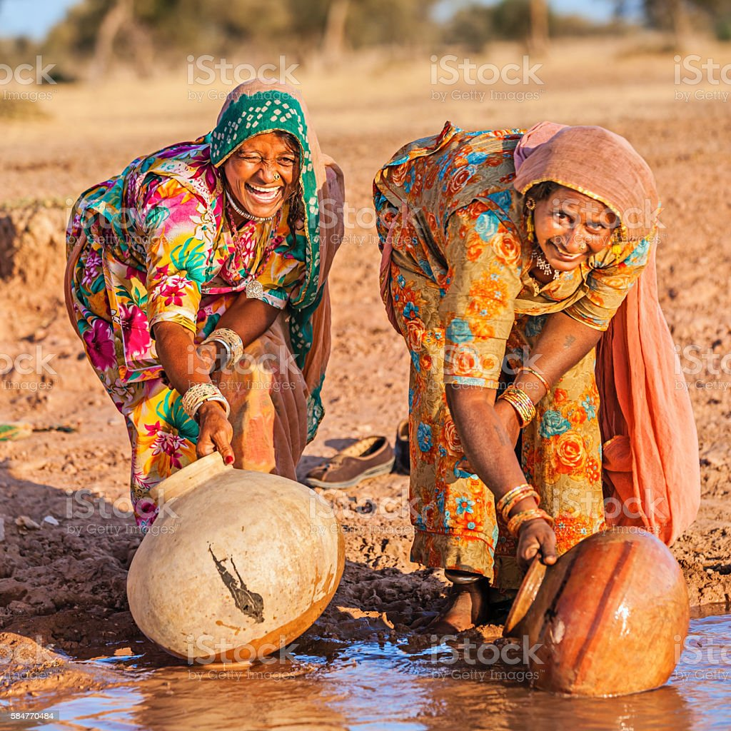 Indian women collecting water from the lake, Rajasthan stock photo