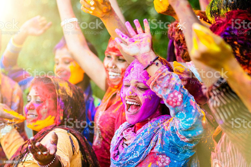 Indian women throwing colored Holi powder stock photo