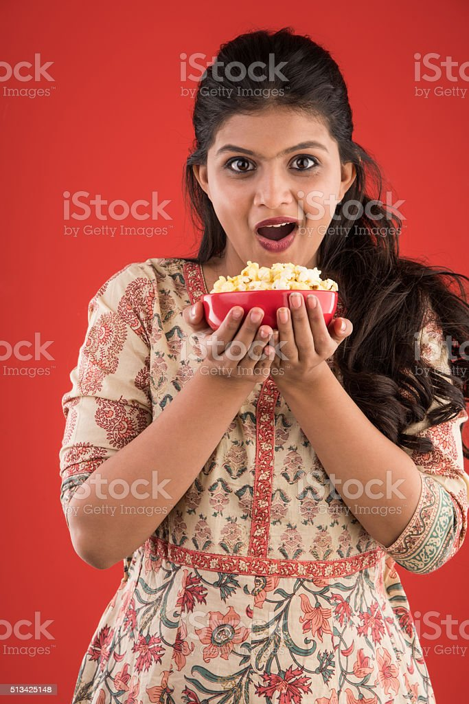 indian young and beautiful girl eating popcorn on red background stock photo