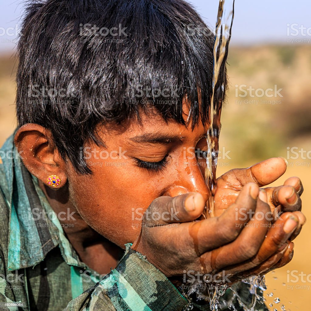 Indian young boy drinking fresh water, desert village, Rajasthan, India stock photo