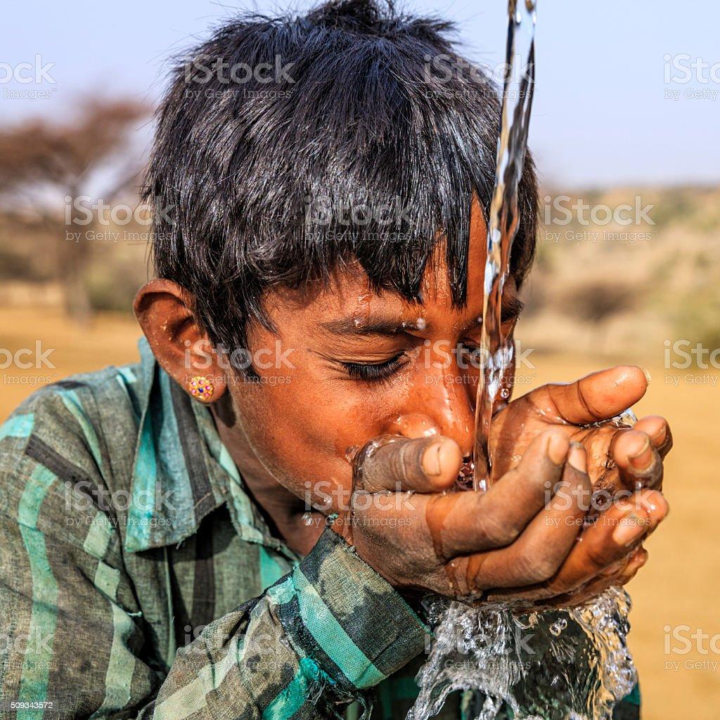 Indian young boy drinking fresh water, desert village, Rajasthan, India stock photo