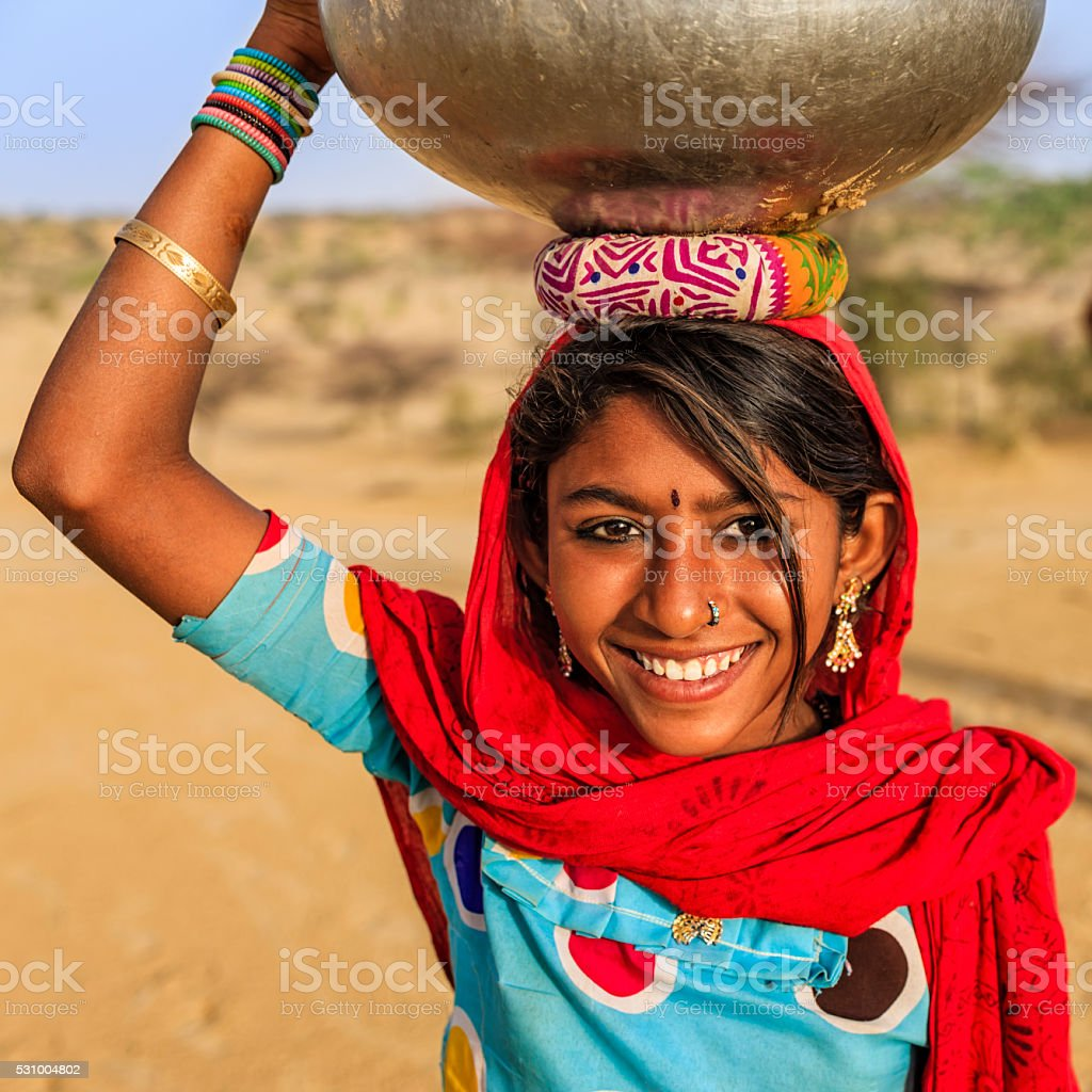 Indian young girl carrying on her head water from well stock photo