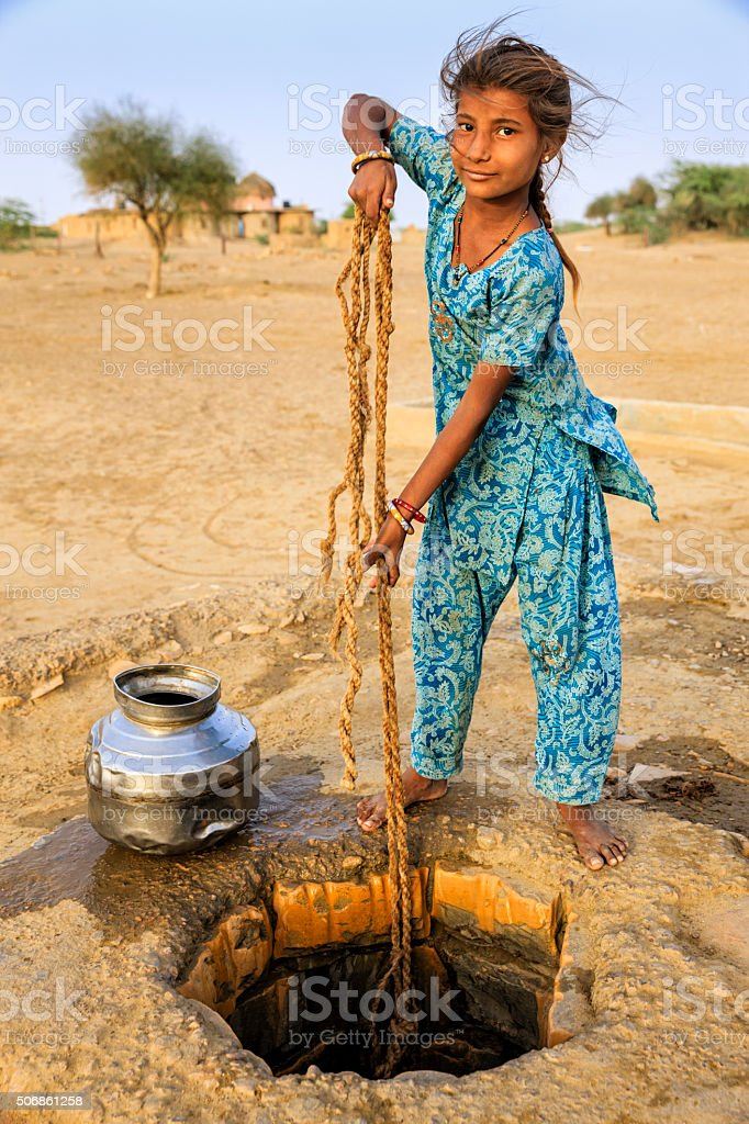 Indian young girl drawing water from a well, Rajasthan stock photo