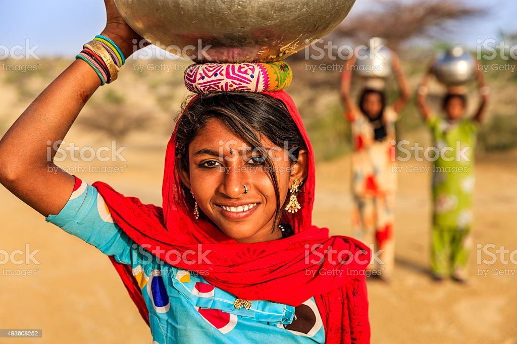 Indian young girls carrying on their heads water from well stock photo