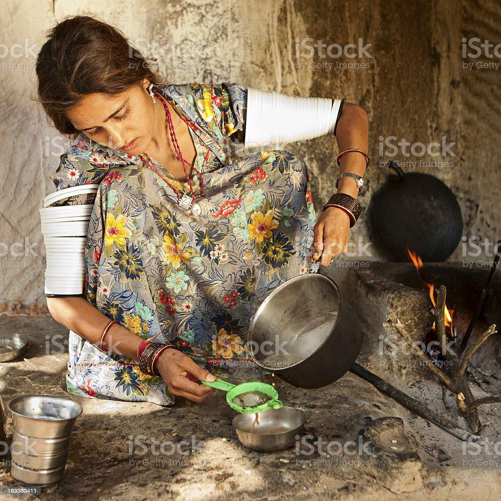 Indian young woman preparing tea. Bishnoi village. Rajasthan. Thar desert. royalty-free stock photo