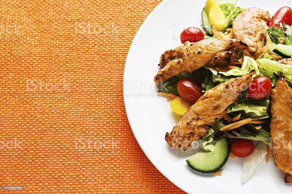 Indian-style spiced chicken salad on orange place mat stock photo