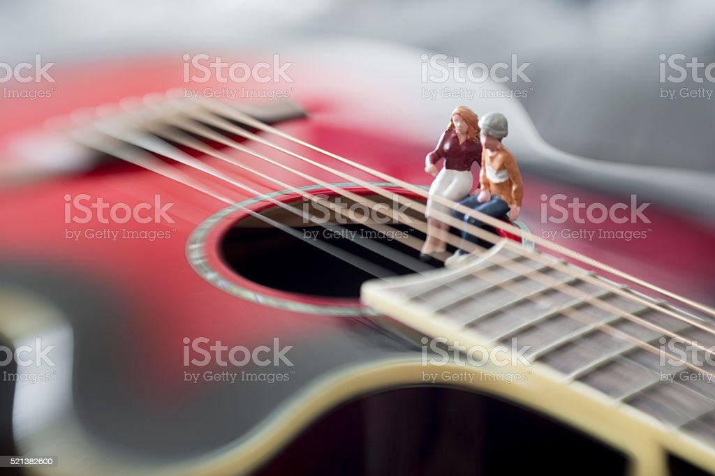 indie teenagers play large guitar together stock photo