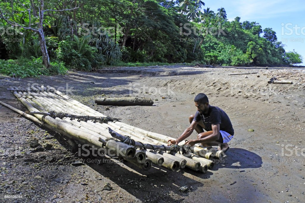 Indigenous Fijan man building a traditional bamboo boat stock photo