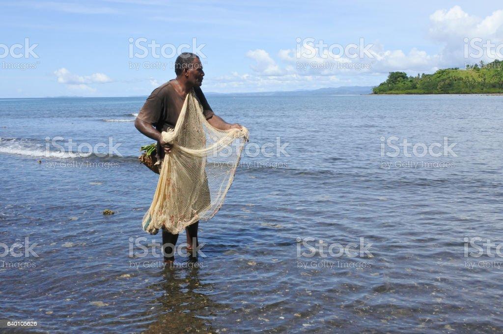 Indigenous Fijian fisherman fishing with net in Fiji stock photo