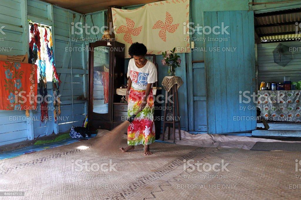 Indigenous Fijian woman cleans her home in Fiji stock photo