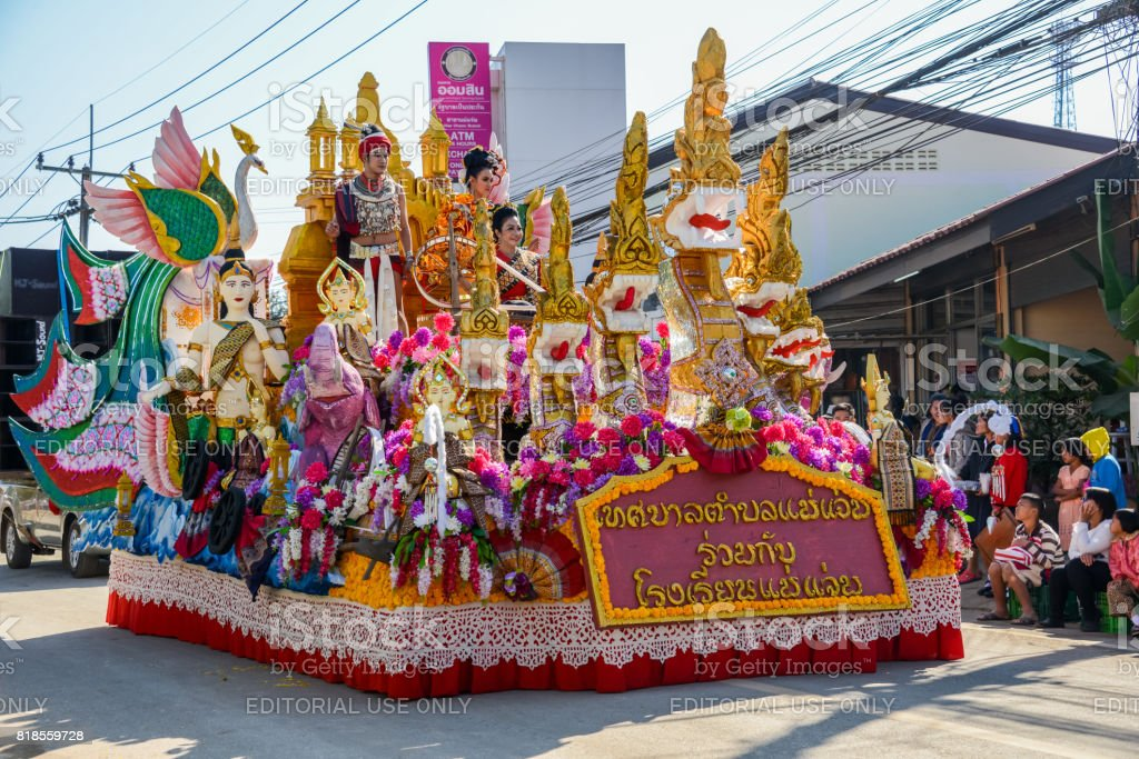 Indigenous people with traitional costume on decorated vehicle with flowers in parade stock photo
