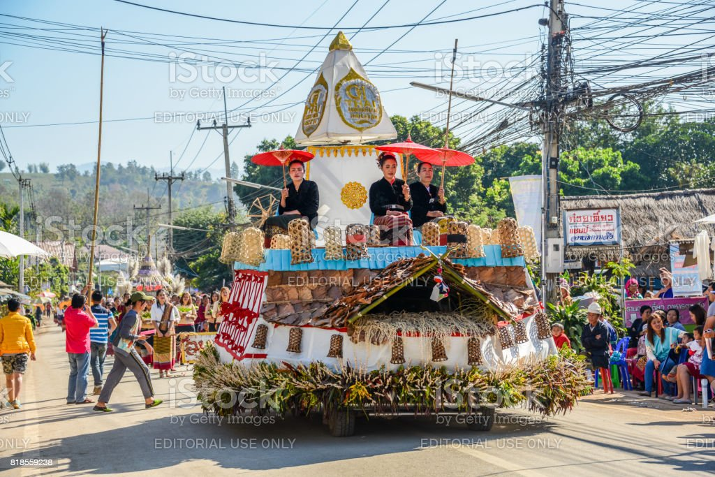 Indigenous women with traitional costume holding red paper umbrella on decorated vehicle with flowers and bamboo basket in parade stock photo