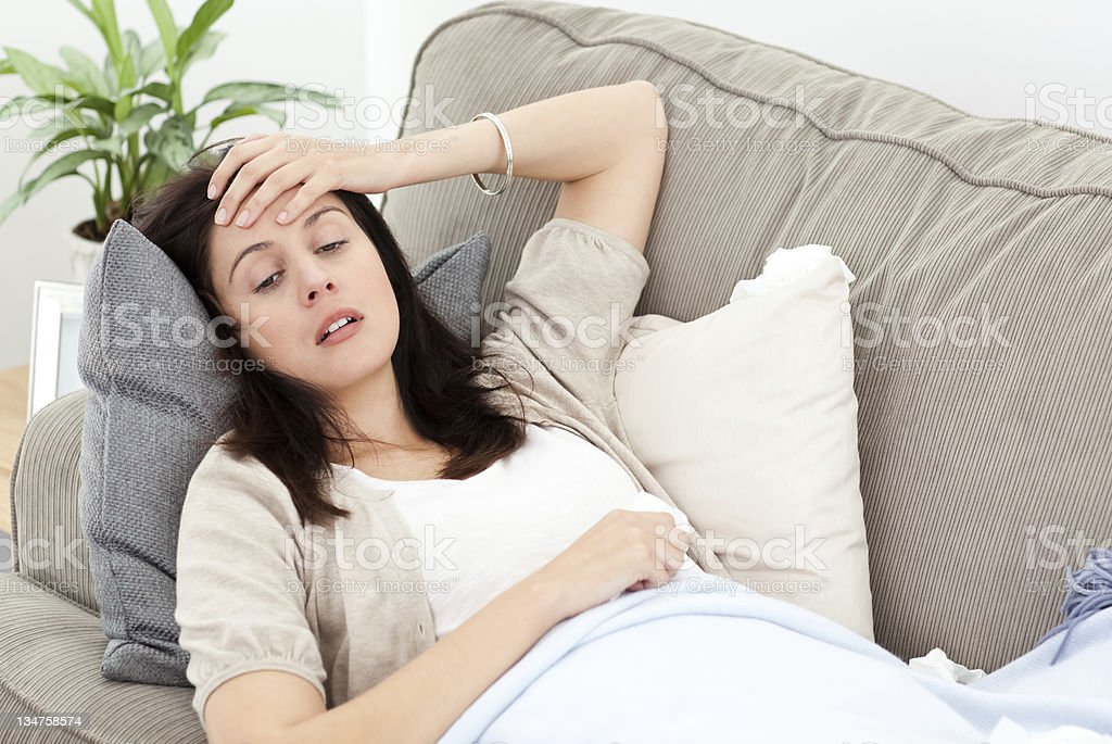 Indisposed woman feeling her temperature stock photo