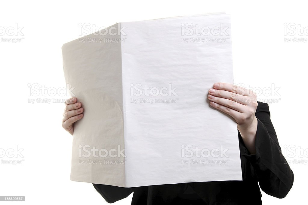 Individual holding blank newspaper in front of their face royalty-free stock photo