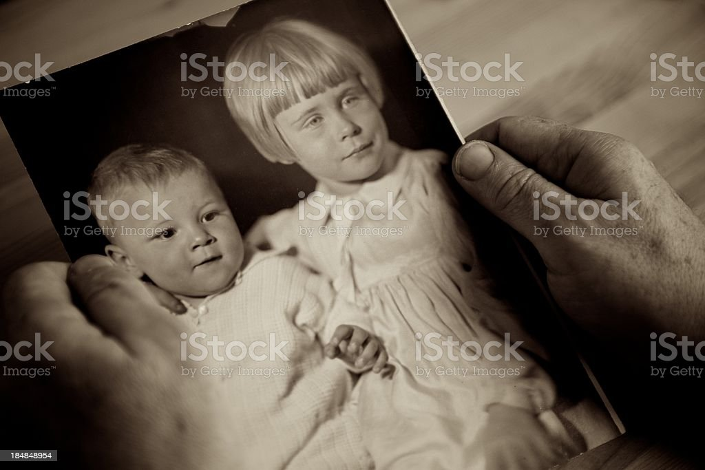 Individual holding picture with childhood memories stock photo