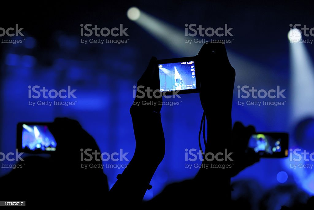 Individual in the dark recording live concert on cell phone royalty-free stock photo