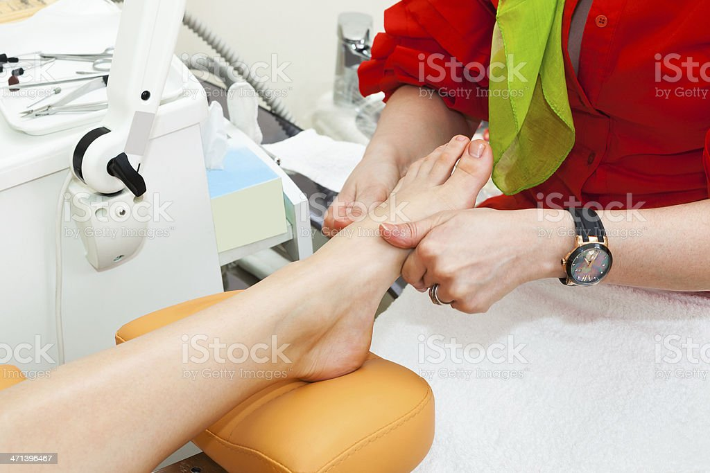 Individual receiving a foot massage stock photo