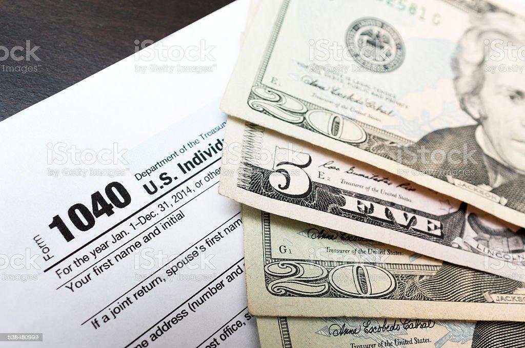 1040 Individual tax return form close up and dollar bils stock photo