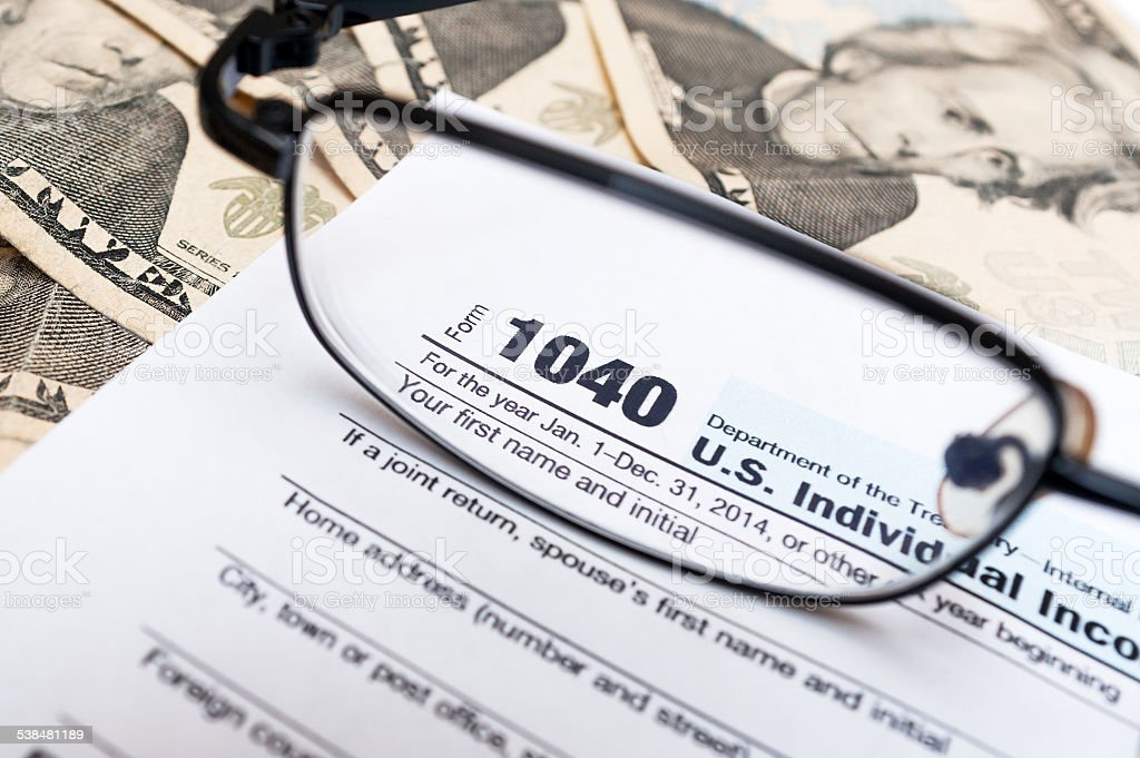 1040 Individual tax return form through eye glasse close up stock photo