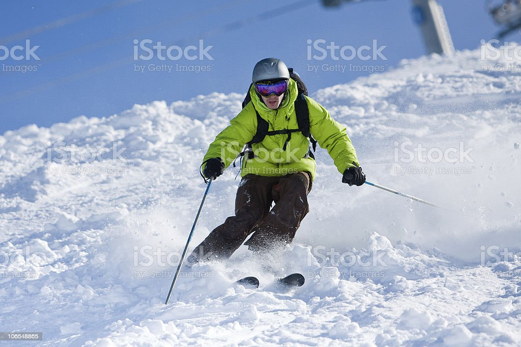 Individual with green anorak skiing off-piste royalty-free stock photo