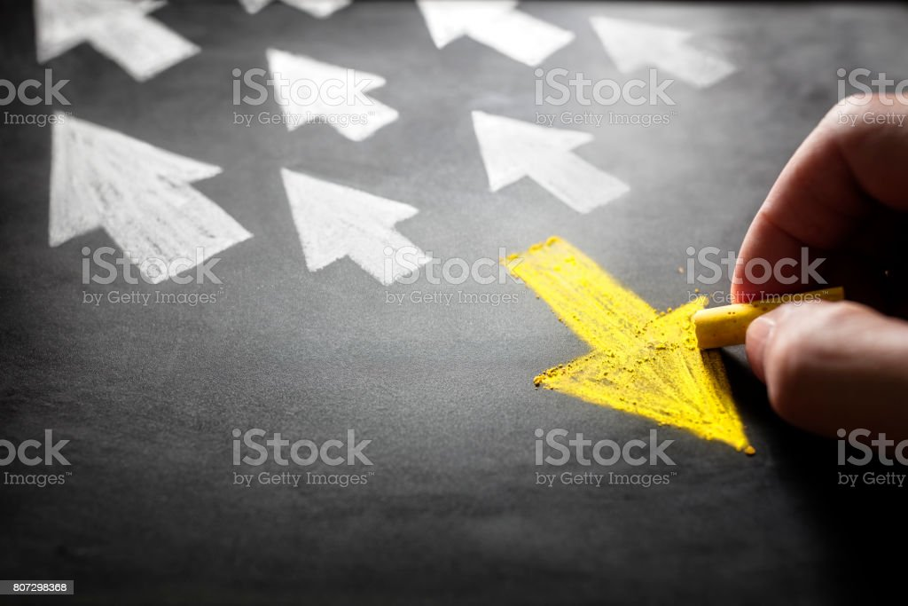 Individuality going a different direction chalk arrow on blackboard stock photo