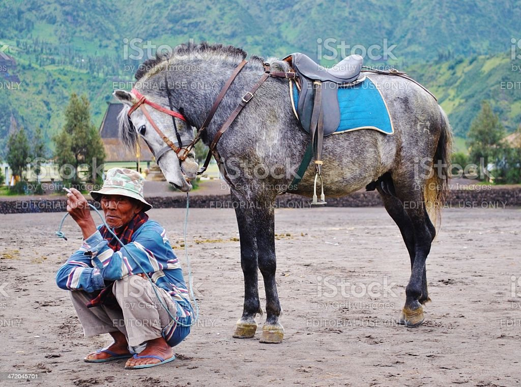 Indonesian Man and Horse at the base of Mount Bromo stock photo