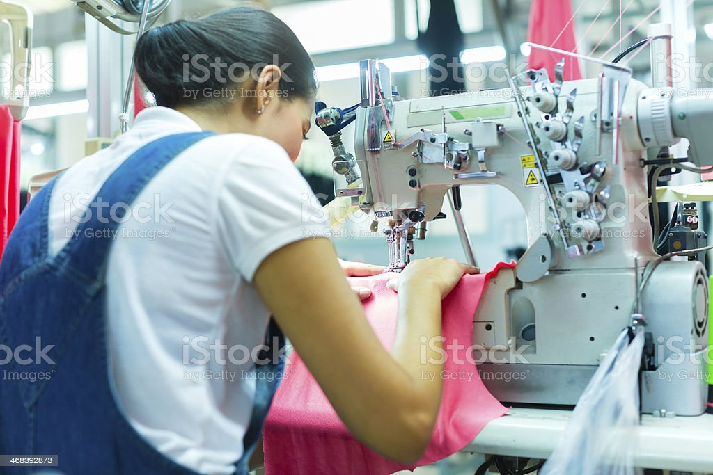 Indonesian seamstress in a textile factory stock photo