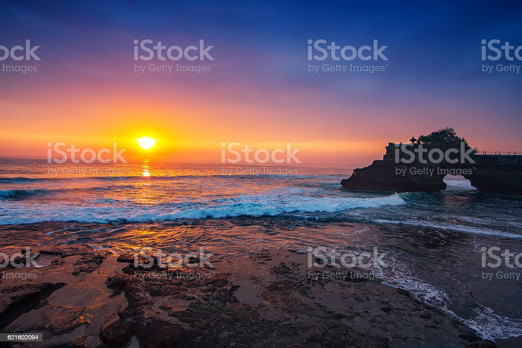Indonesian temple in sea with tourist. stock photo