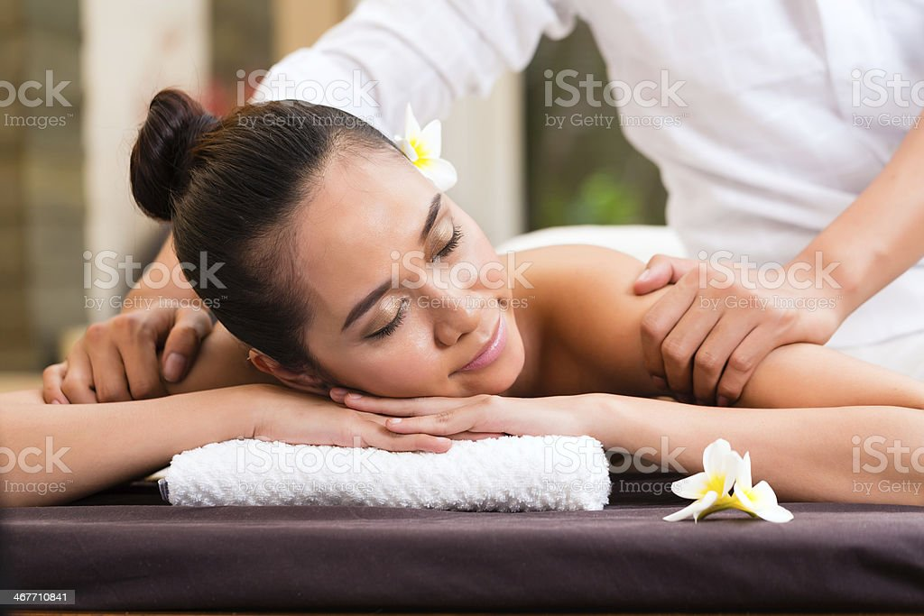 Indonesian woman wellness massage in spa stock photo