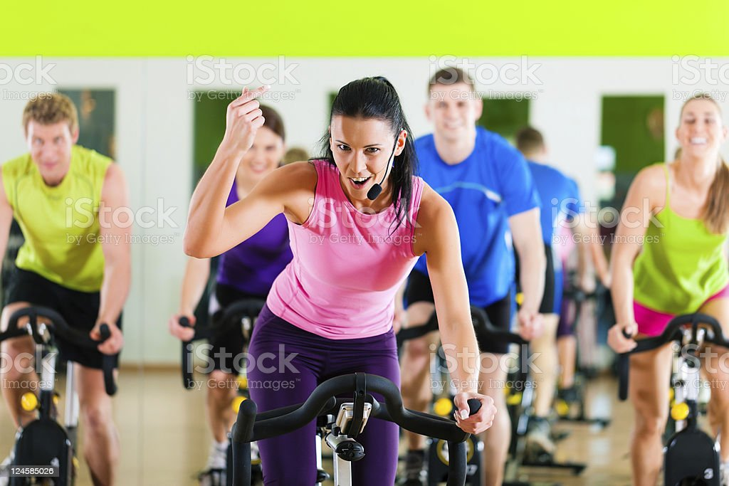 Indoor bycicle cycling in gym stock photo