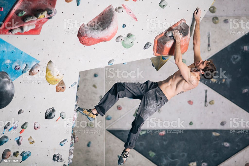 Indoor climbing in the bouldering gym wall. stock photo
