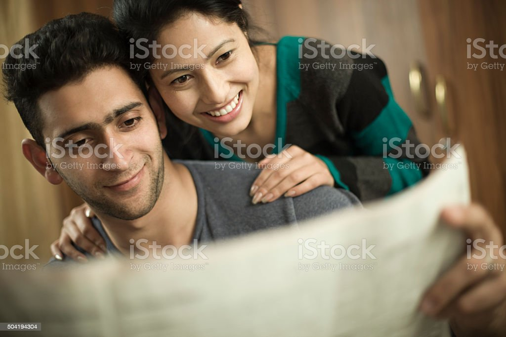 Indoor, happy young couple reading something exciting in newspaper together. stock photo