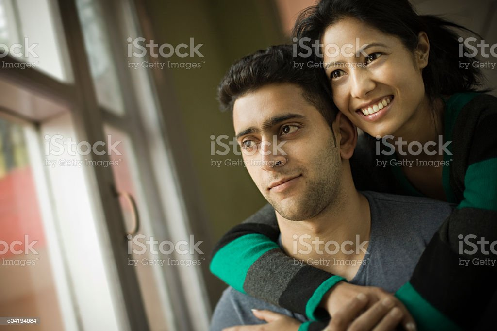 Indoor, happy young couple together looking at view outside window. stock photo